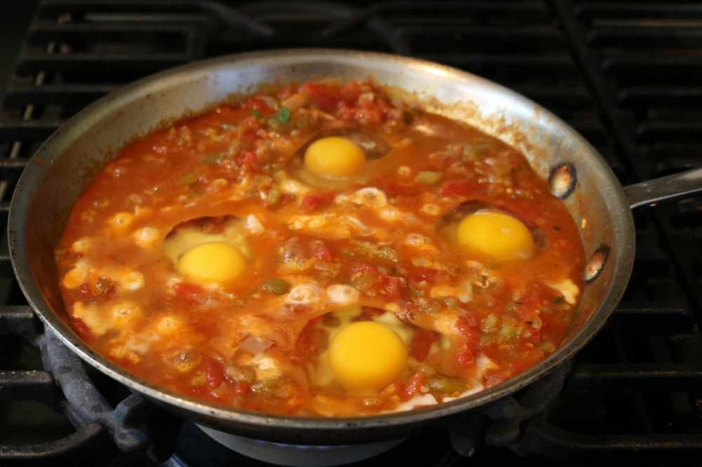eggs just beginning to simmer in the tomato and chili sauce
