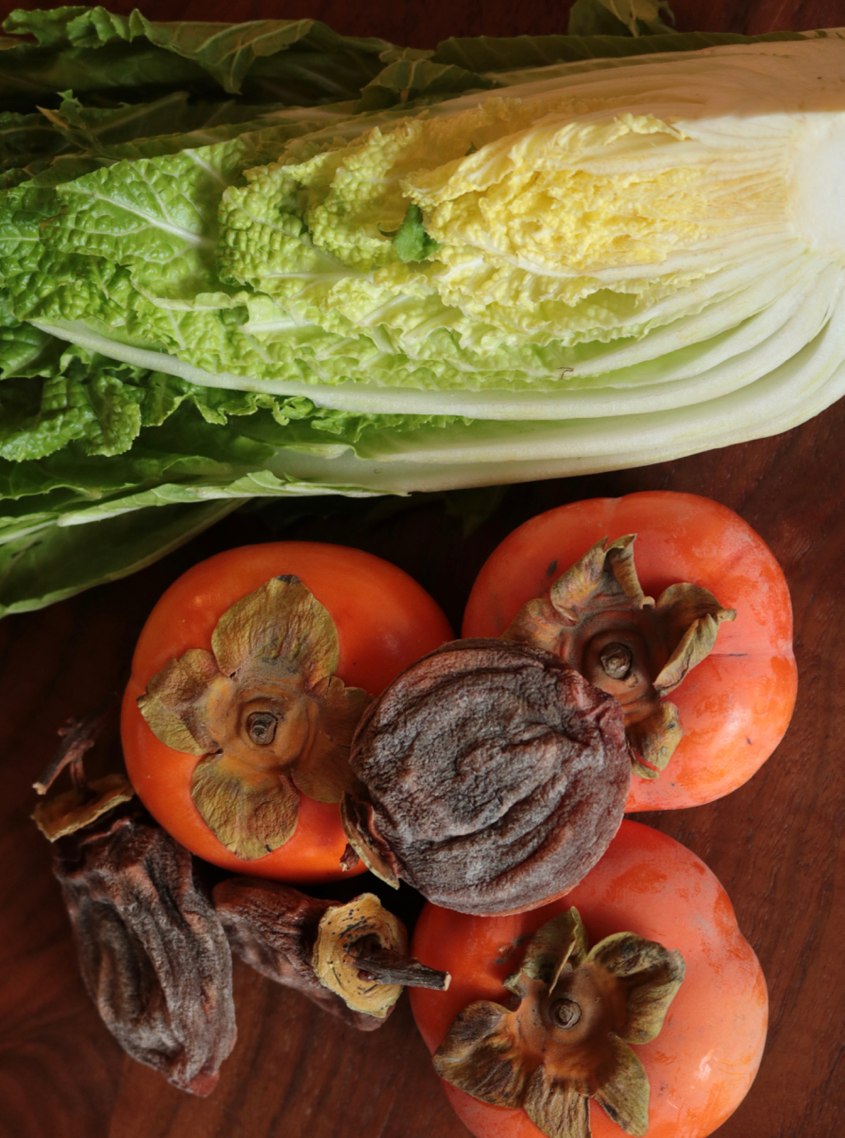 Napa cabbage, bright orange Fuyu persimmons, and dried Hachiya persimmons